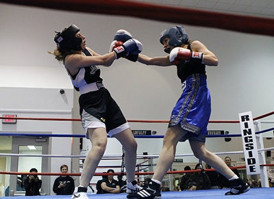 Two women in a boxing ring. They are both wearing protective gear and are mid-fight.