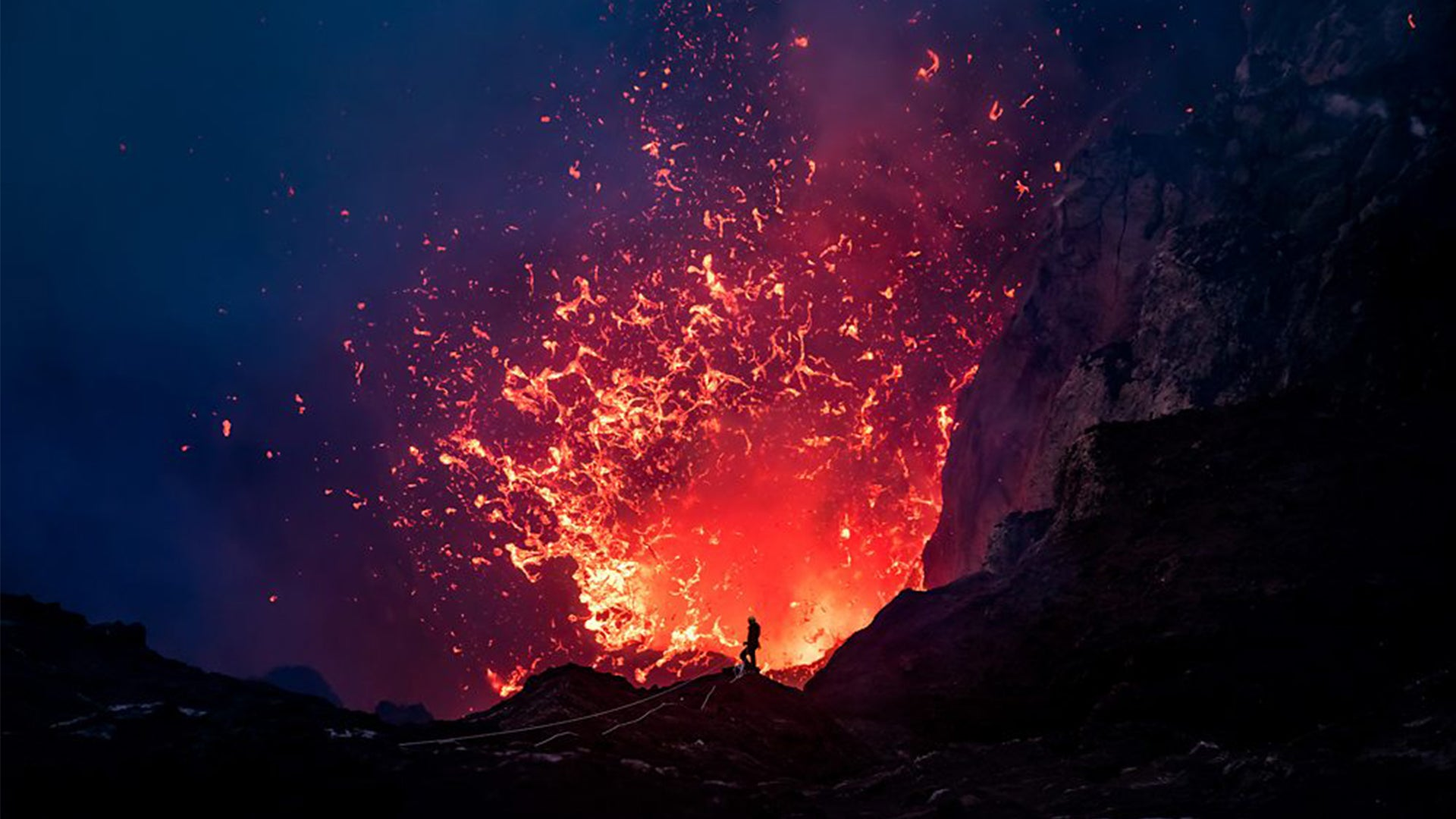 A photograph of a volcano spewing lava. A man's silhouette is seen against the lava's glow.