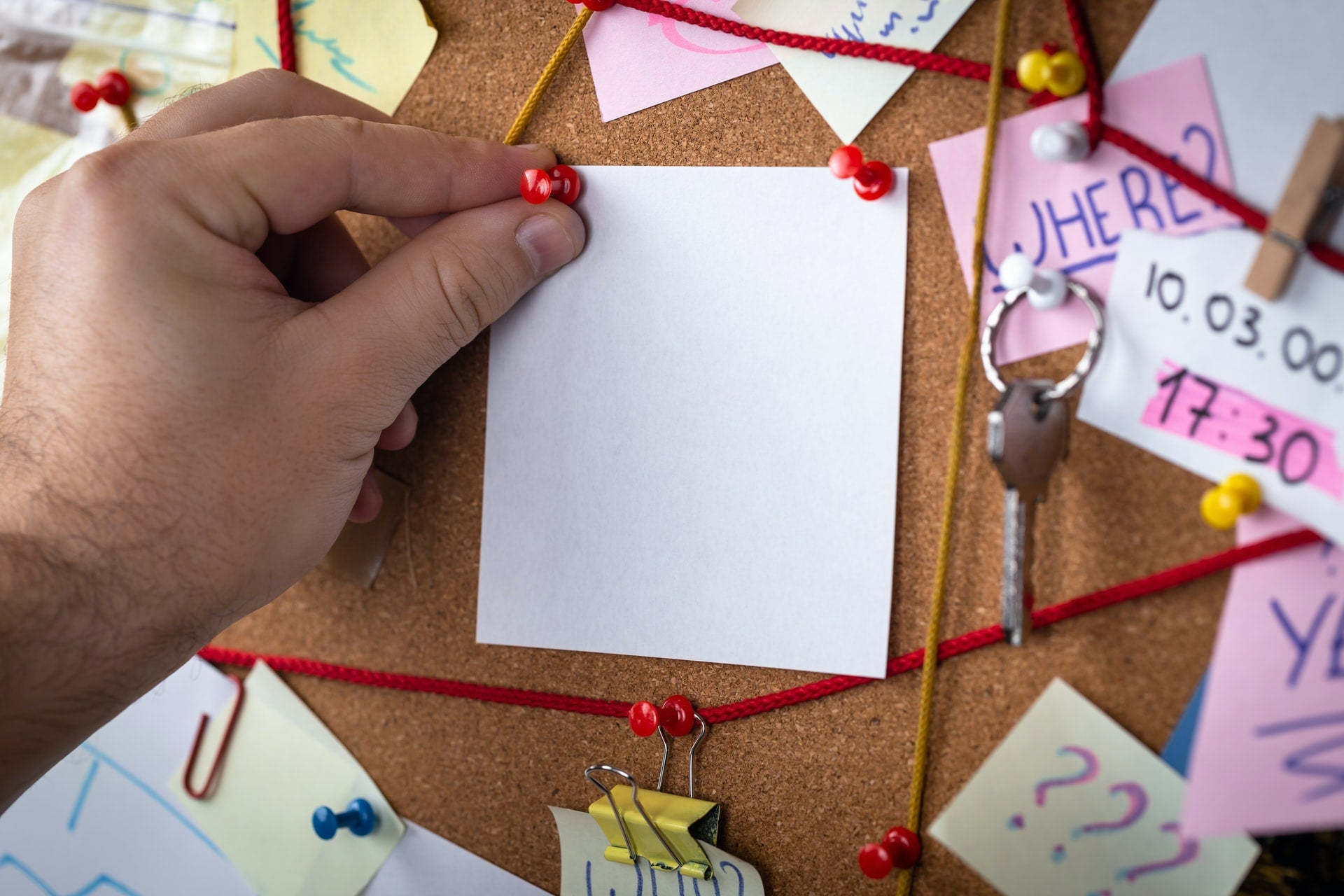 A picture of a hand pinning a post-it to a detective board. Lots of other notes are pinned around it, and red string is pinned in such a way it connects some notes