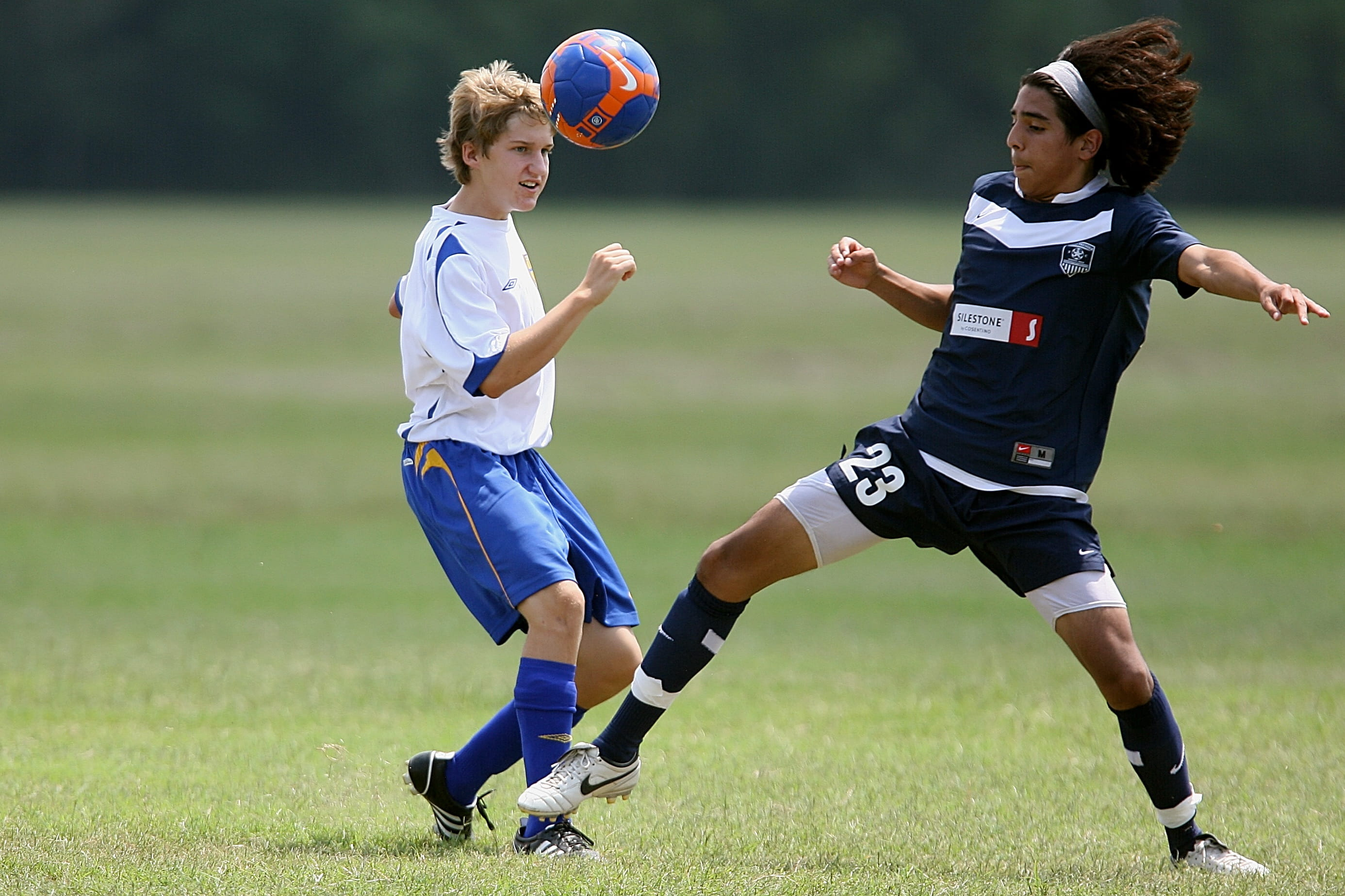 Two teenagers playing football