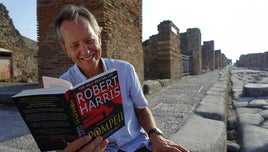 Richard E Grant smiling, and reading an open copy of the book: Pompeii