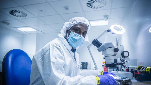 A forensic investigator wearing a white gown, hat, and a mask sits at a microscope