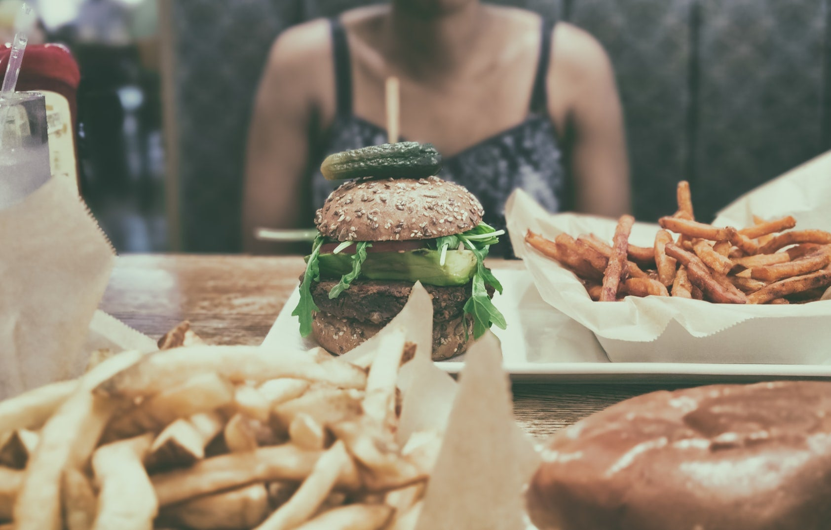 A person sits at a table that has a burger and chips on it