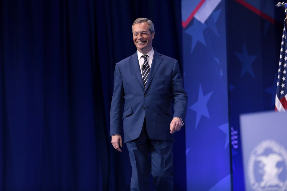 Nigel Farage walks on stage at a conference