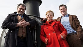 The presenters of Full Steam Ahead stood, smiling, in front of a steam train