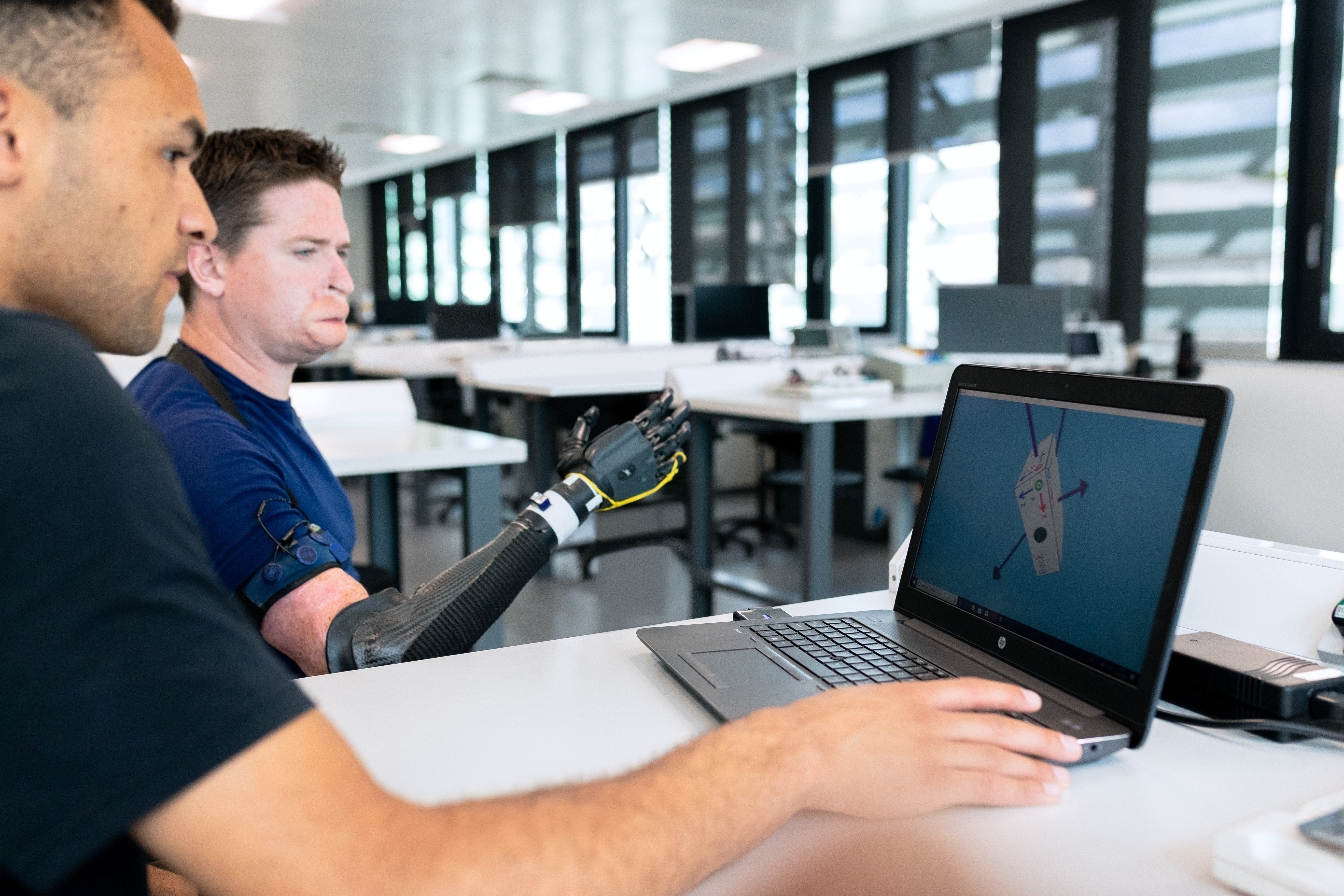 A designer and patient work on bionic arm