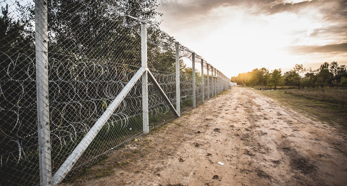 A dirt road bordered by a fence stretches away into the distance