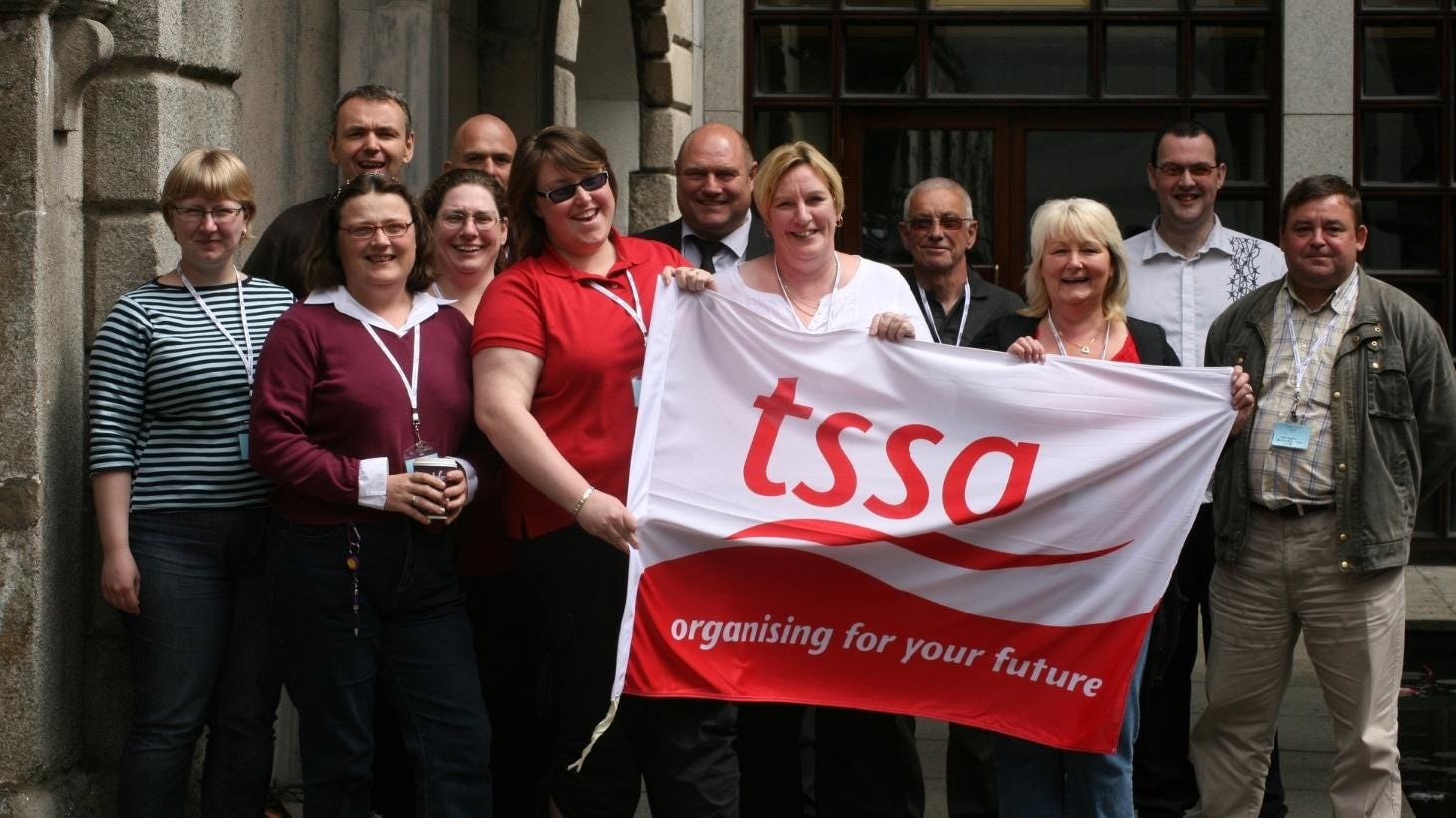 TSSA reps holding a TSSA logo flag