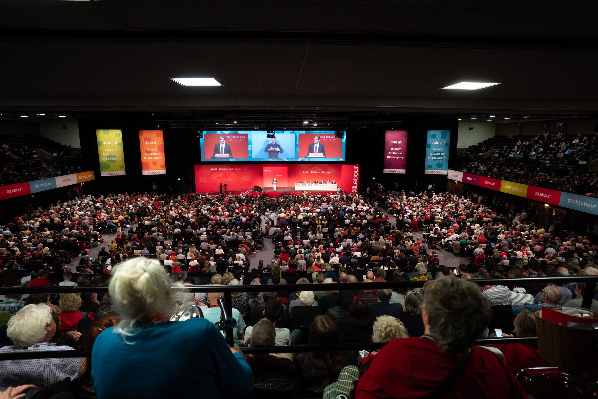 Head-on shot of Labour Party conference hall, Brighton 2019, showing rows of seated delegates, stage and big screen