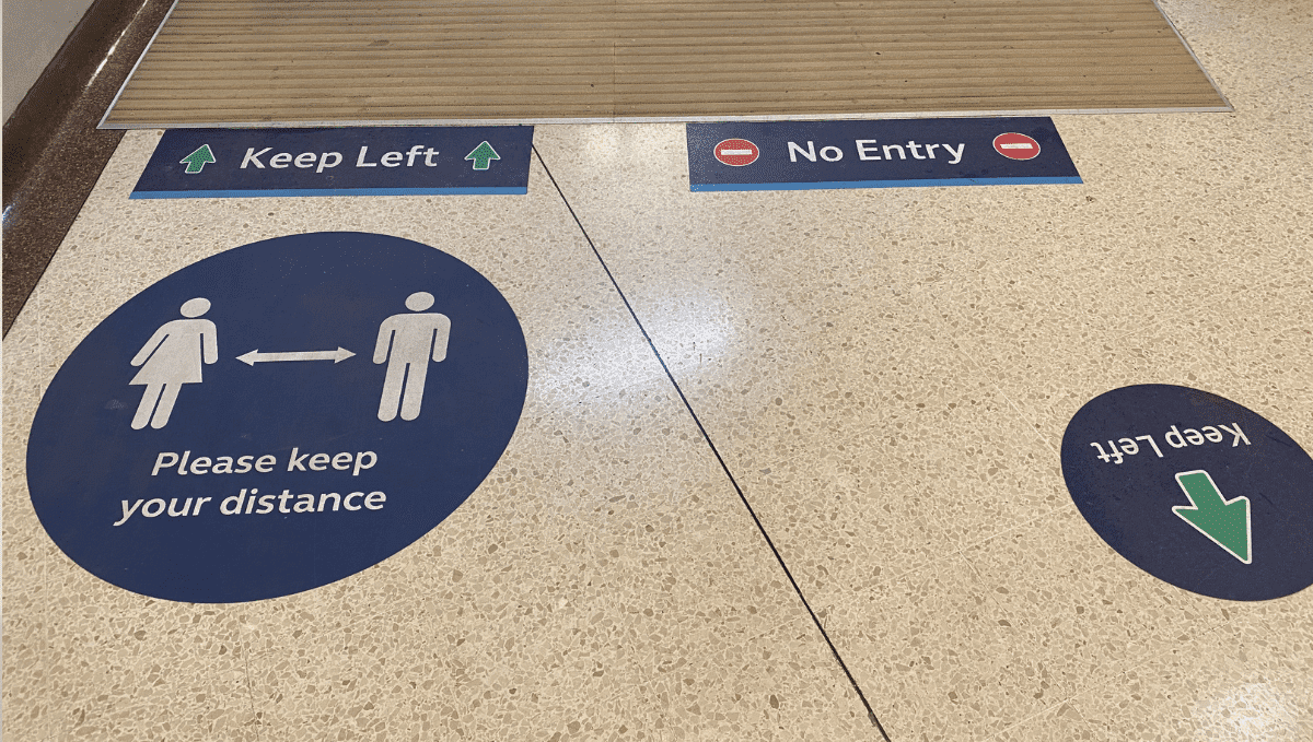 Social distancing signs on station floor
