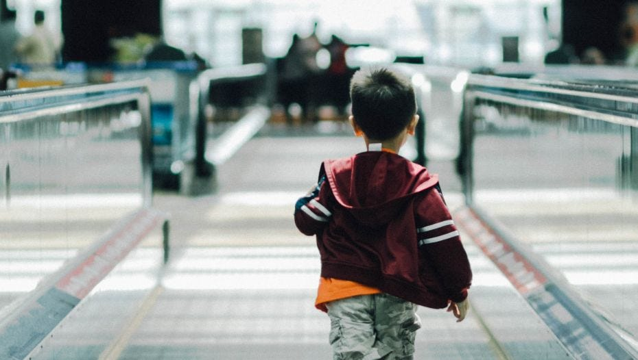 Boy running through station