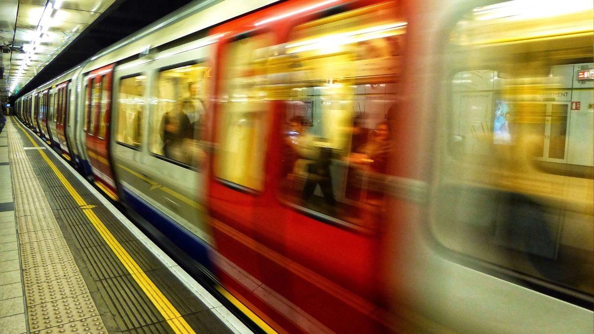 Tube train moving through underground station, TfL