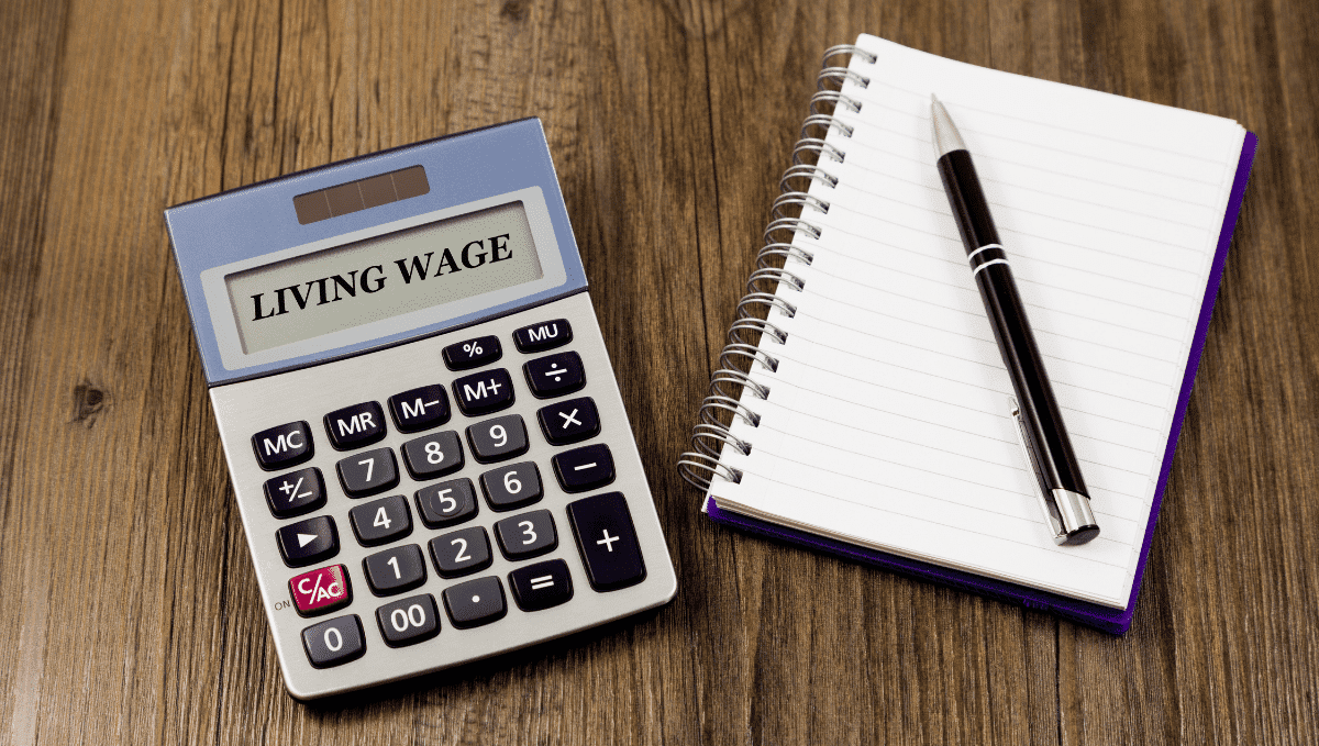 Photo of calculator displaying 'living wage' on screen and a pen and paper