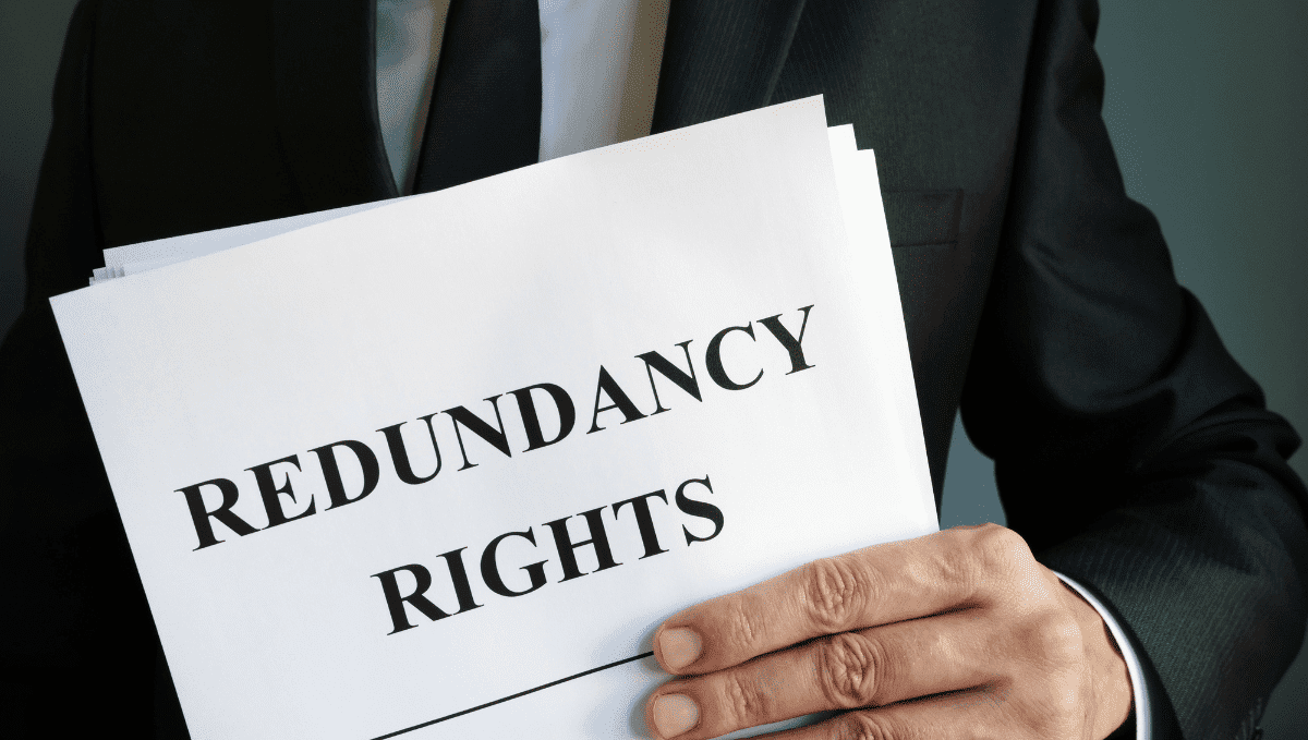 Man in a suit holding a sign which reads: redundancy rights