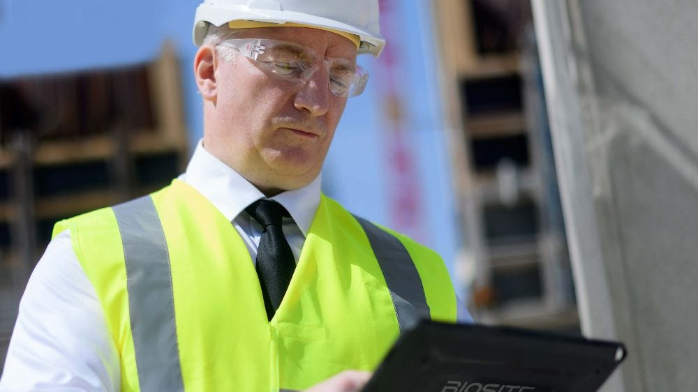 Health and safety inspector wearing yellow vest, safety specs and hard hat on HS2 site with tablet.