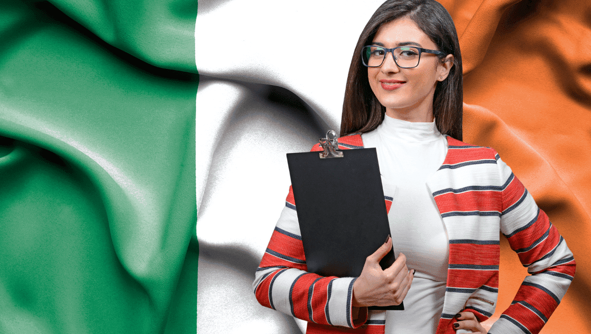 Woman with clipboard standing in front of Irish flag.