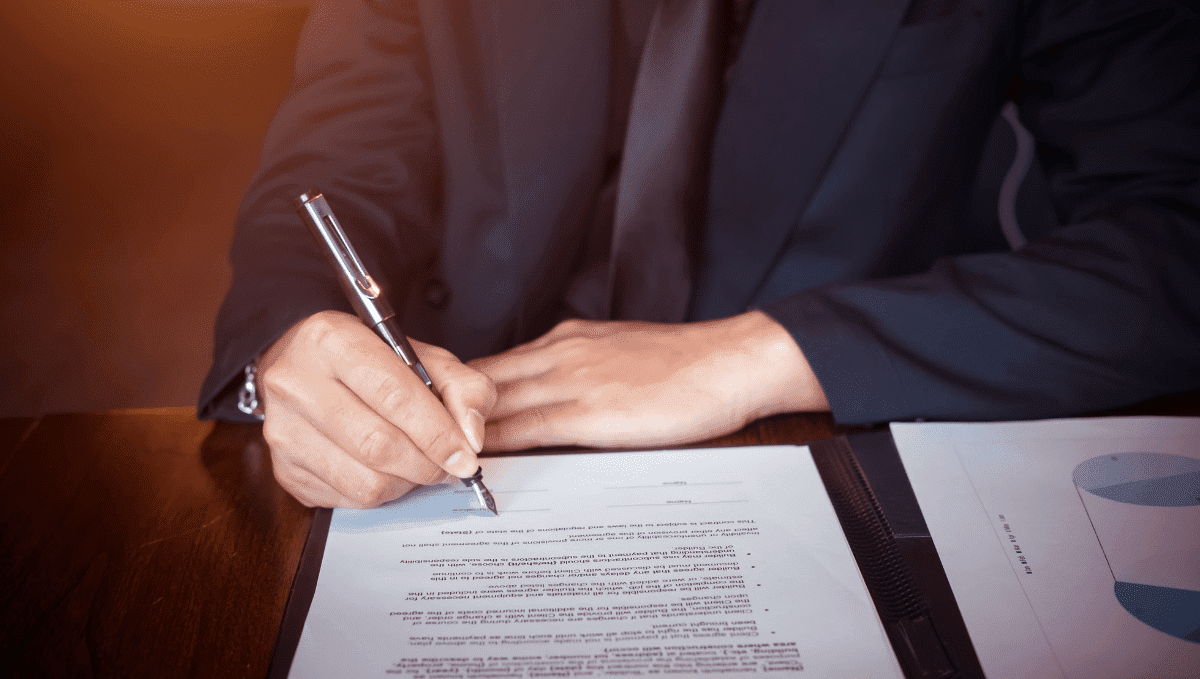 Man signing a document at a desk