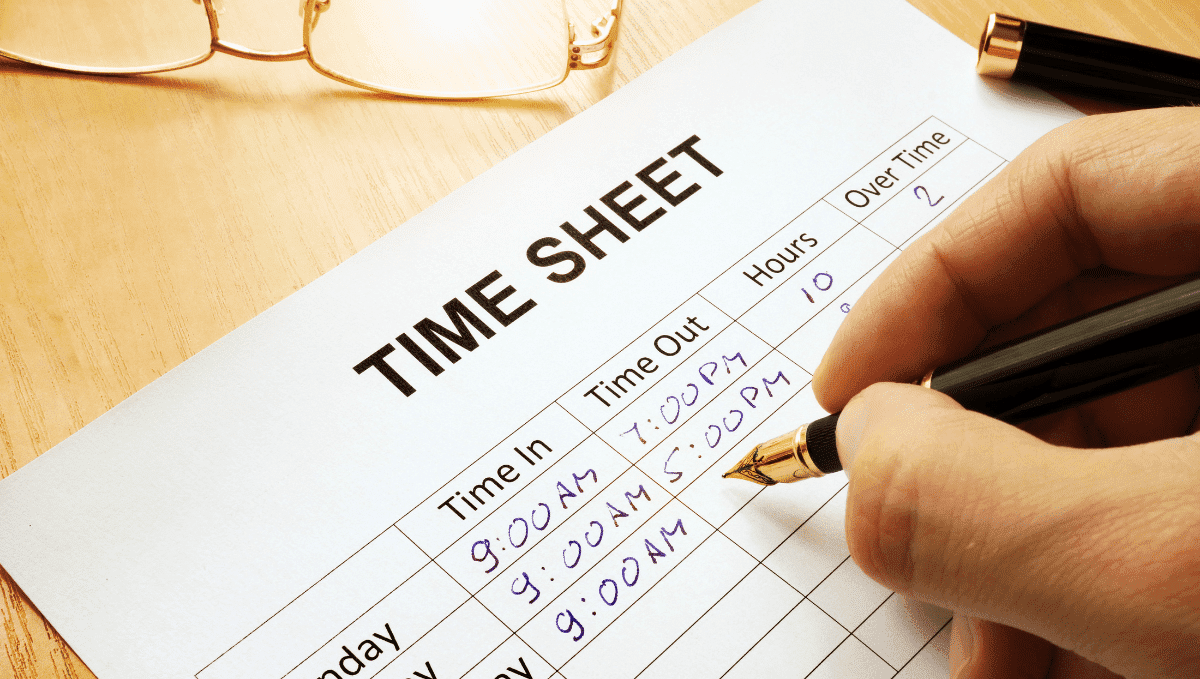 Photo of someone filling in a time sheet with a pen.