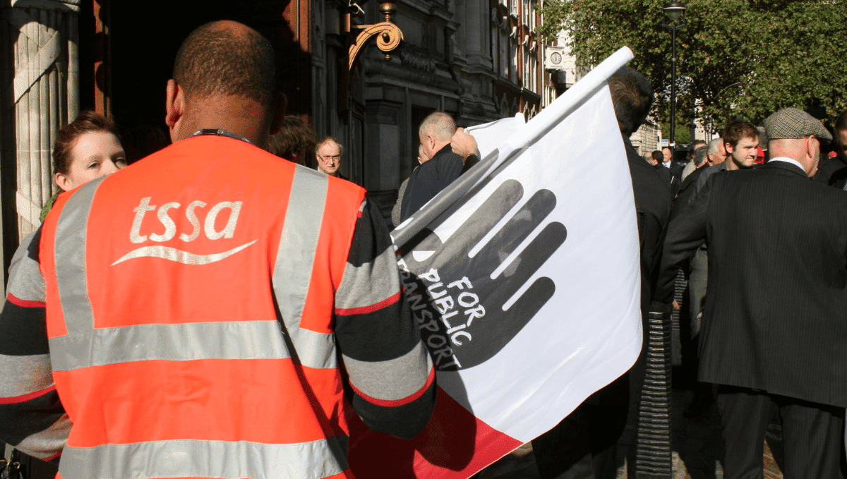 Person wearing a high vis TSSA jacket and holding a campaign flag