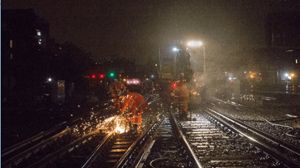 Network Rail engineers working on tracks at night with metal sparks shining in darkness