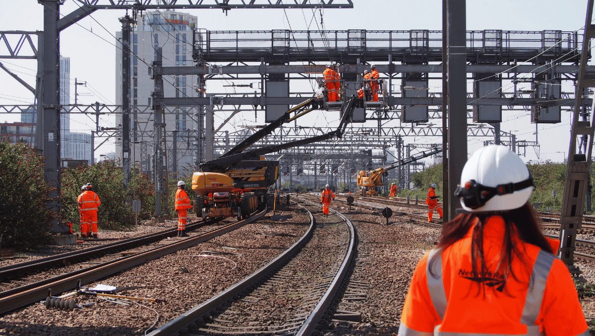 Network Rail workers in orange high vis and hard hats working on tracks and overhead lines