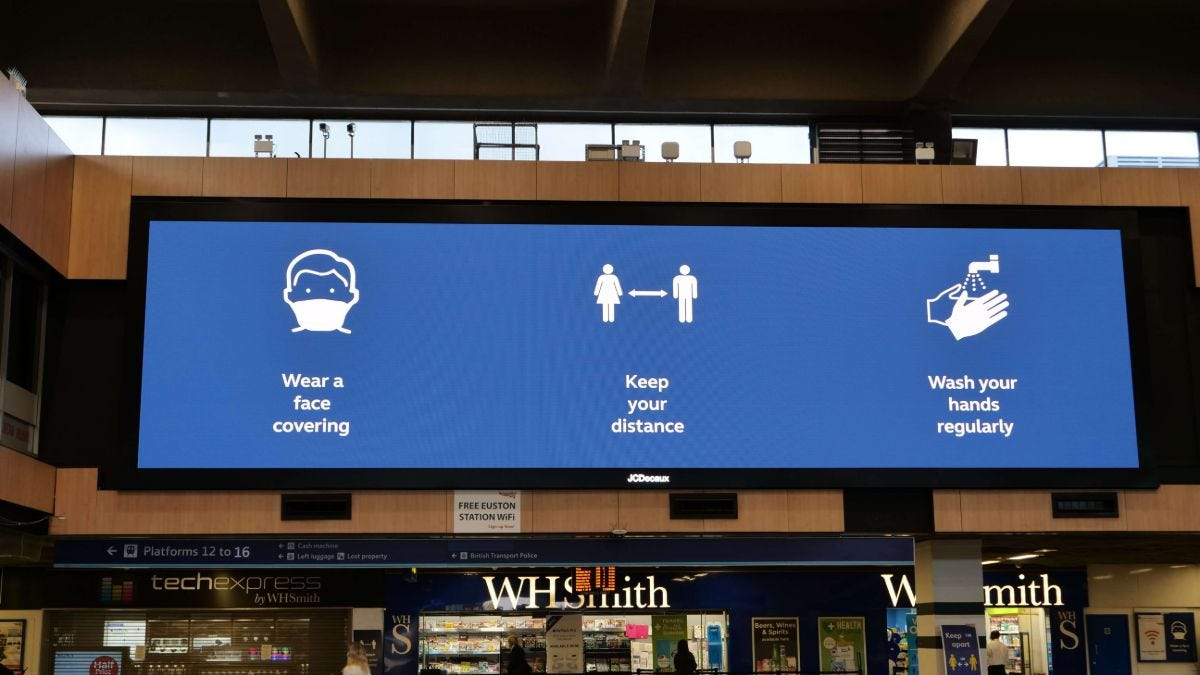 Covid advice digital sign in rail station showing hands, face, space