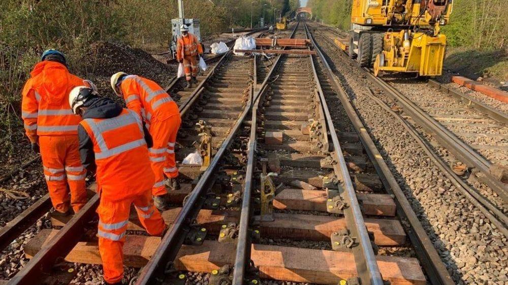 Network Rail engineers in orange high vis working on rail tracks