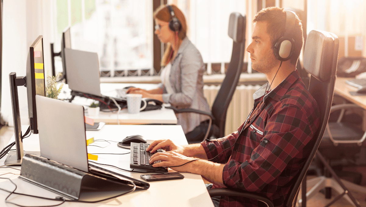 Two office workers at desks with laptops and headphones