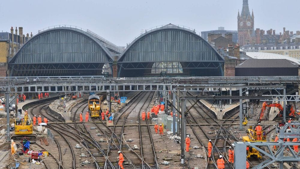 Network Rail engineers wearing high vis and helmets working on multiple tracks outside of a big station