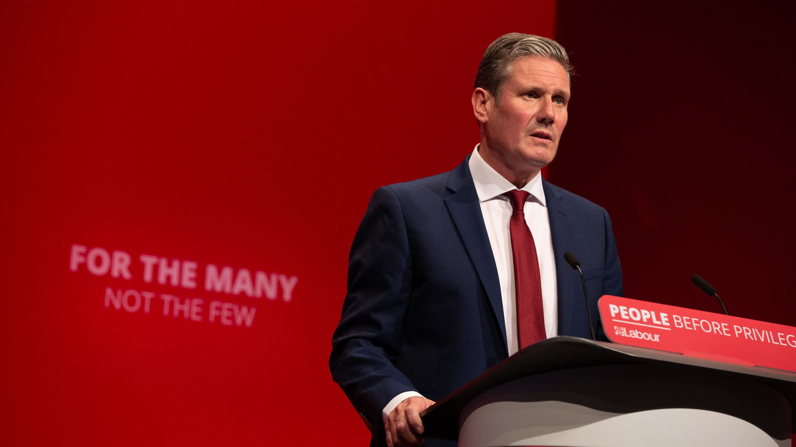 Keir Starmer speaking at the podium at Labour Party conference with red background showing slogan: For The Many Not The Few