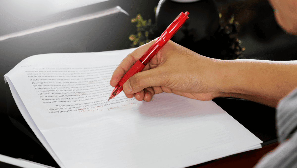 Photo of someone correcting a printed document with red pen