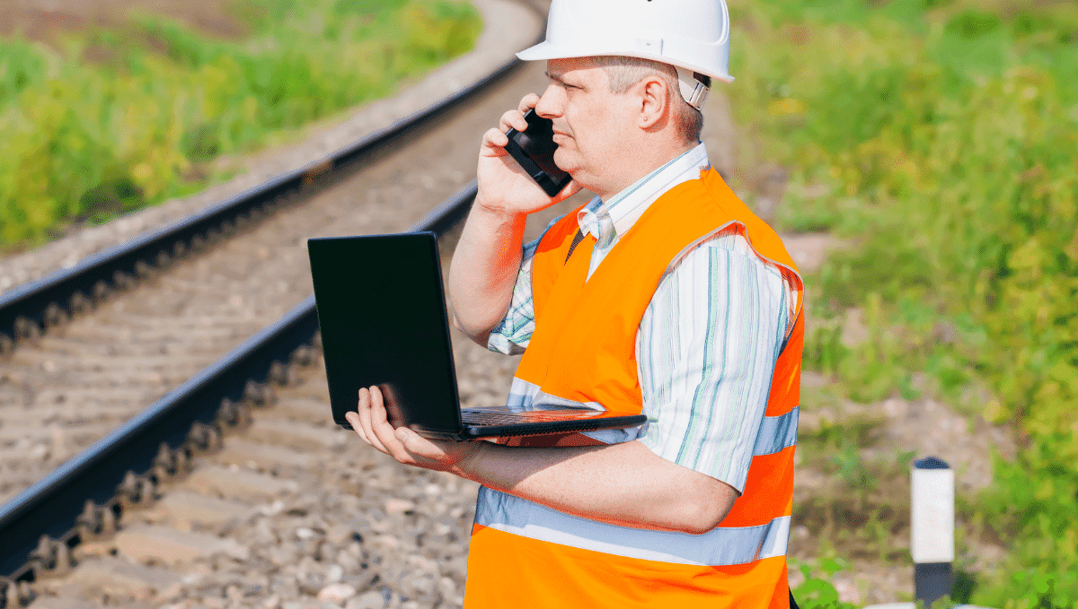 Rail worker in orange high vis trackside with laptop