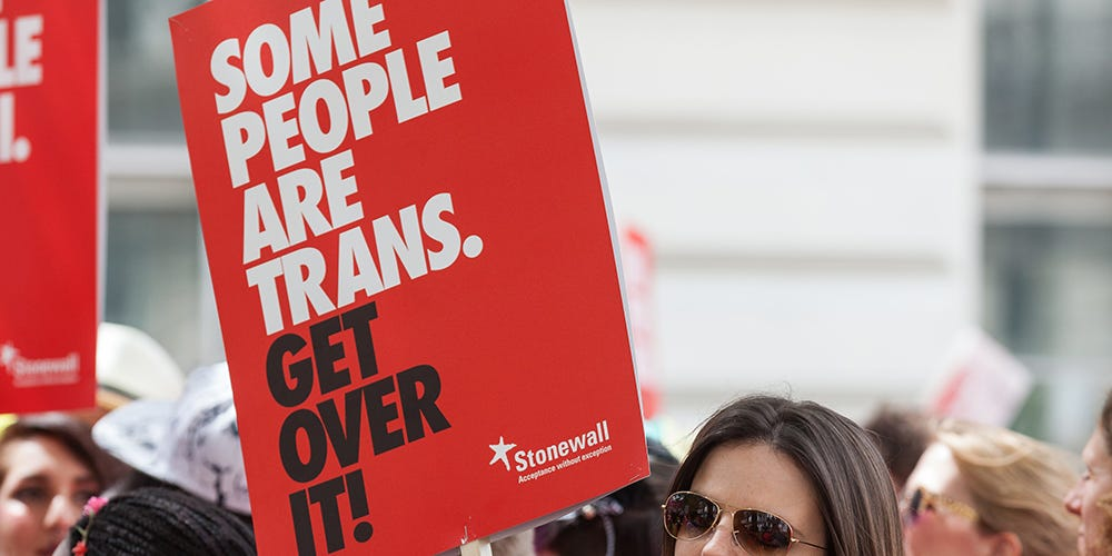 """Stonewall© """"Some people are trans"""" sign being held"""