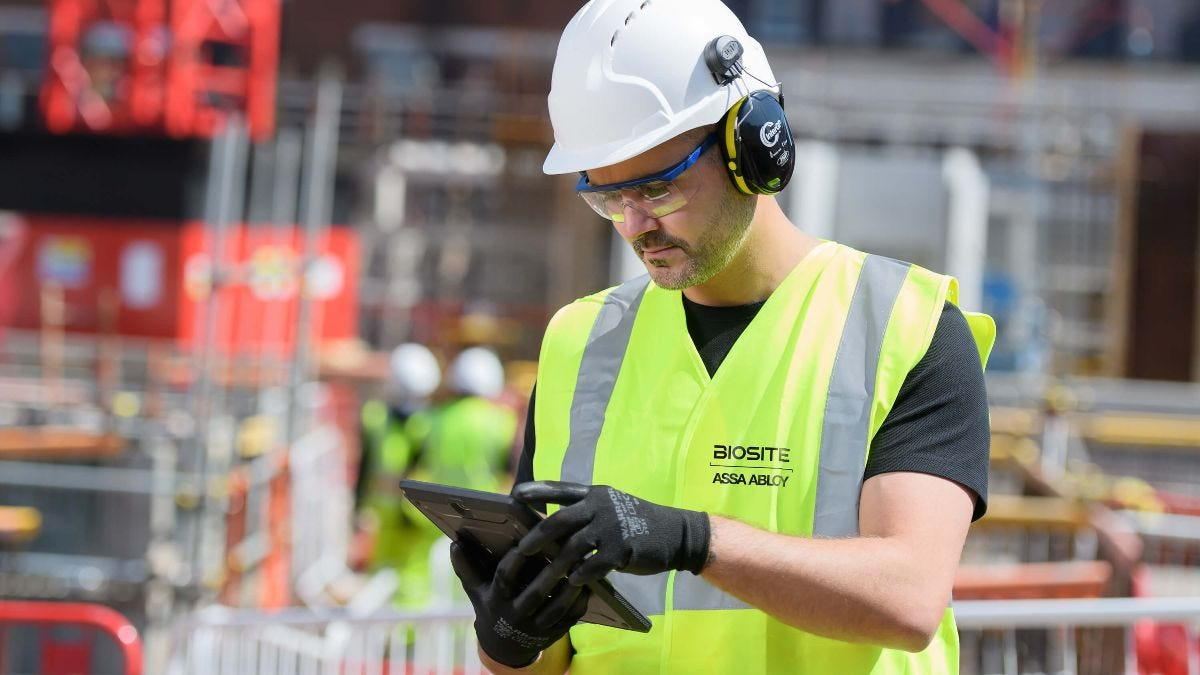 Health and safety inspector wearing yellow vest, safety specs, ear defenders, gloves and hard hat using tablet.