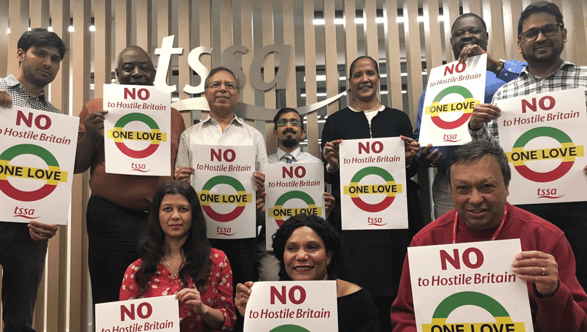 Photo of people holding up 'No to hostile Britain' posters from TSSA BAME Emix group at TSSA HQ