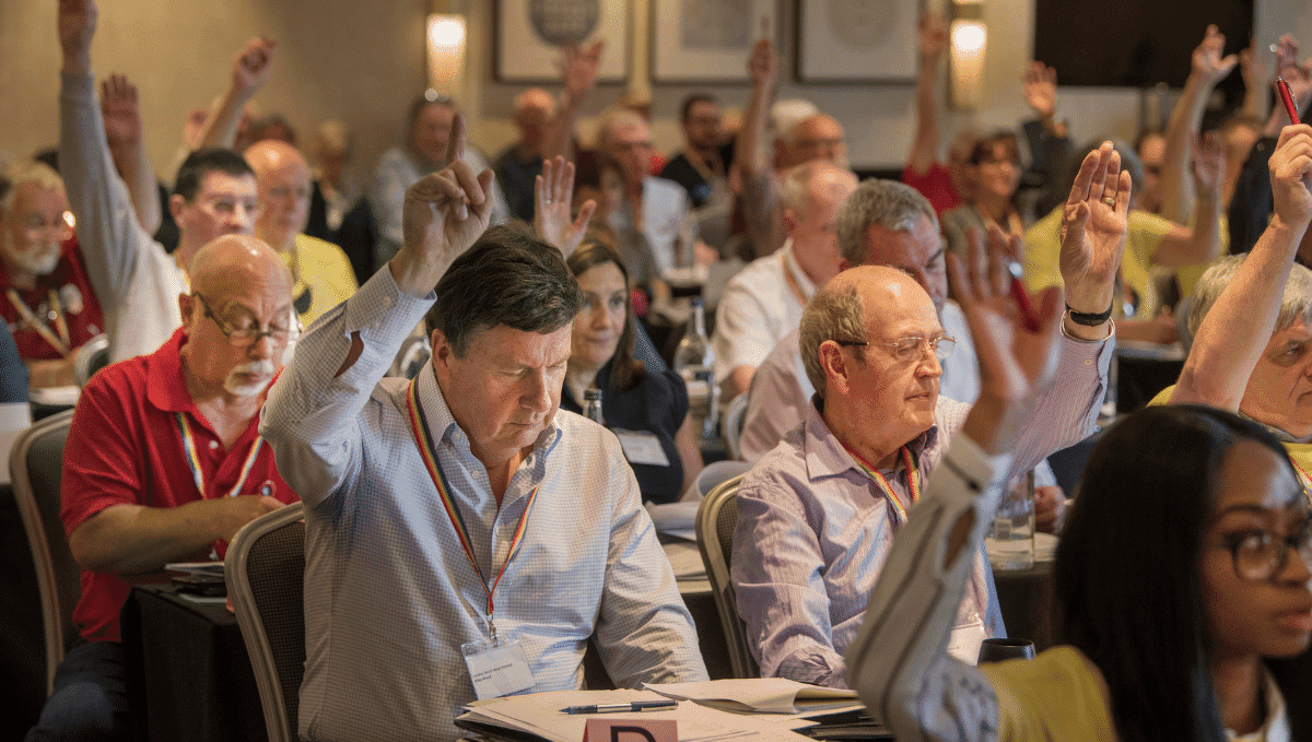 TSSA conference delegates voting with hands in the air