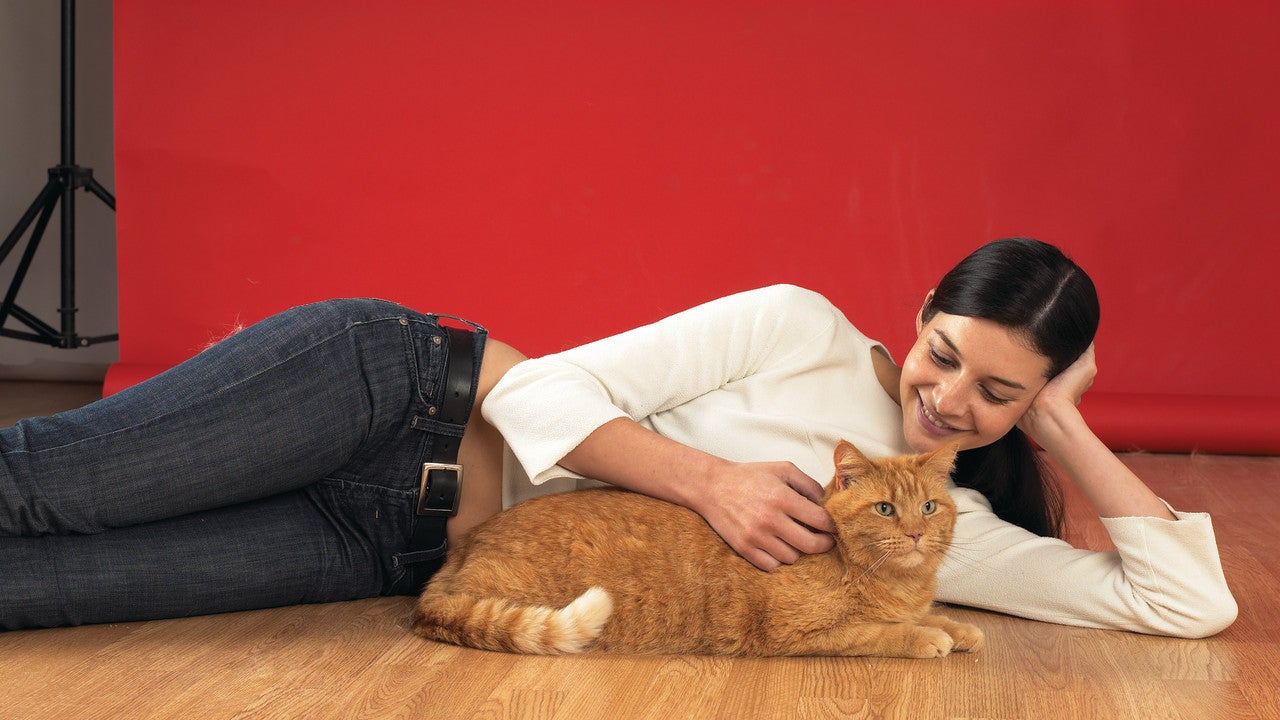 Woman laying on floor patting cat in front of red screen.