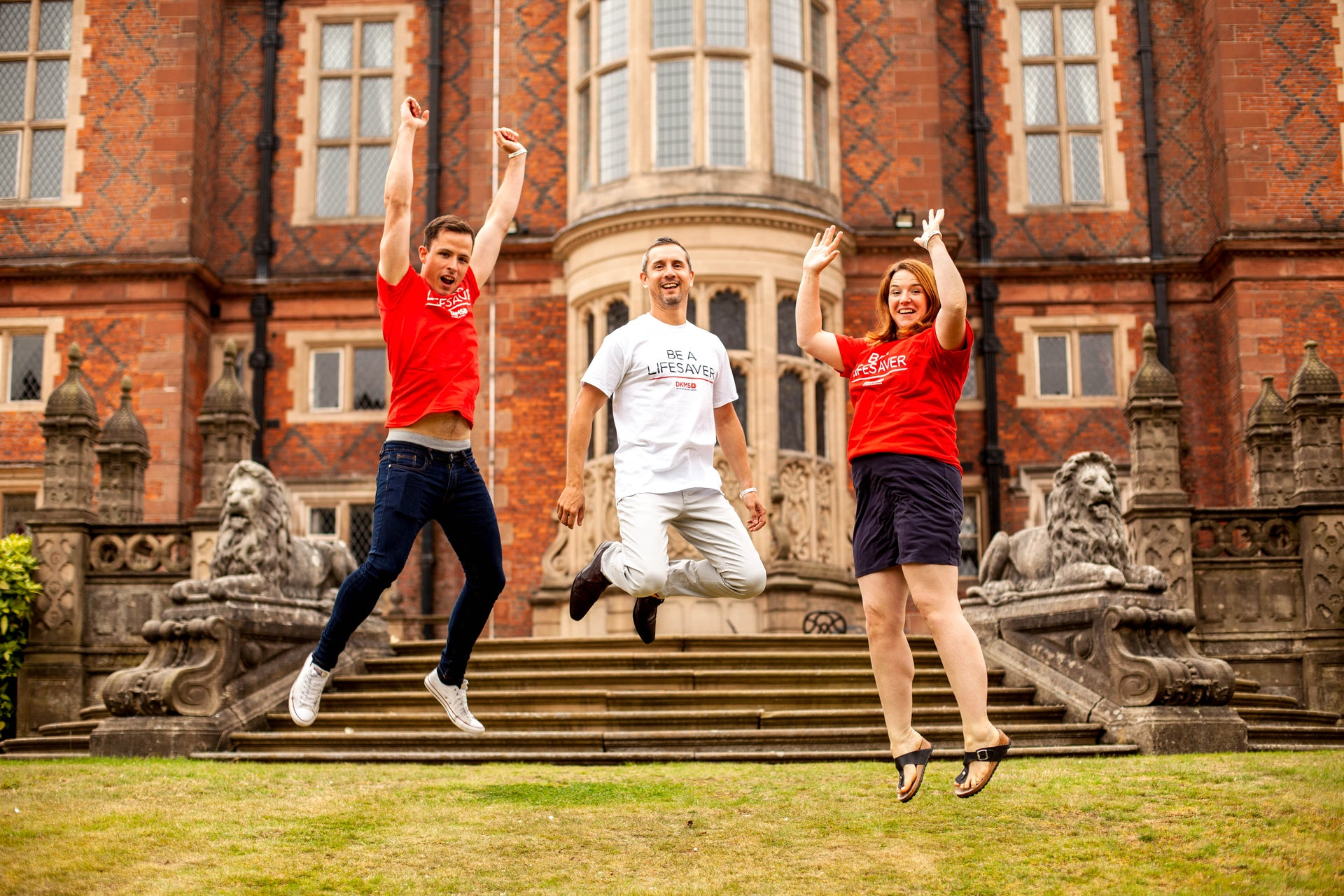 Three people jumping outside Crewe Hall