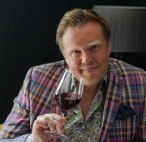 Image of Olly Smith holding a glass of wine smiling into the camera