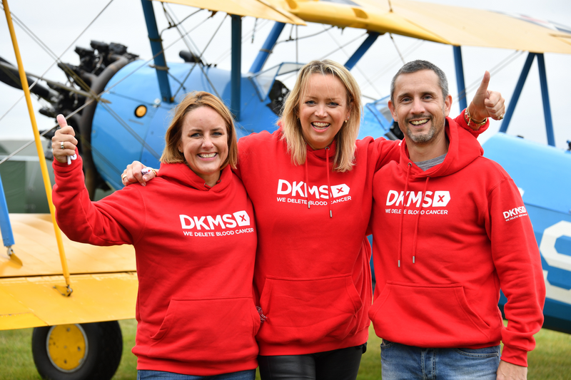 L - R Sally Hurman, Lisa Jackson and Peter McCleave in red DKMS jumpers in front of the aircraft