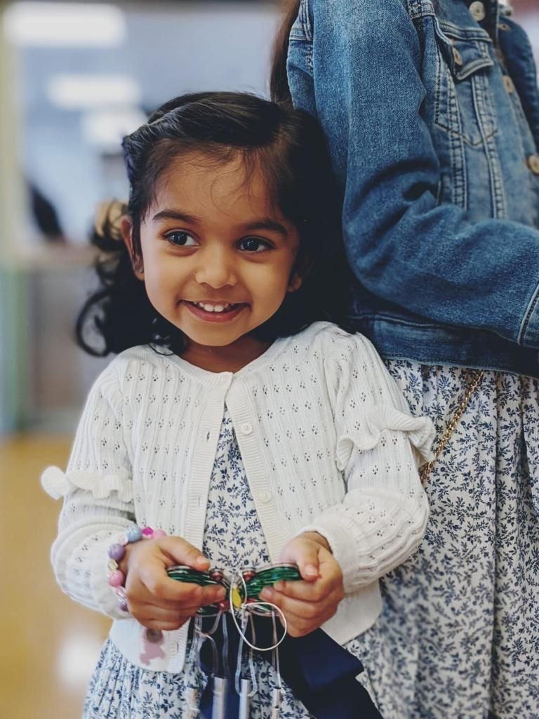 Esha holding a toy butterfly smiling