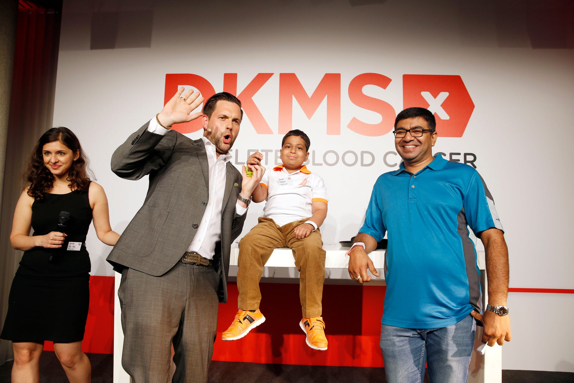 Four people in front of the DKMS logo smiling and cheering