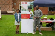 Arya and Levi Roots stood either side of a DKMS banner