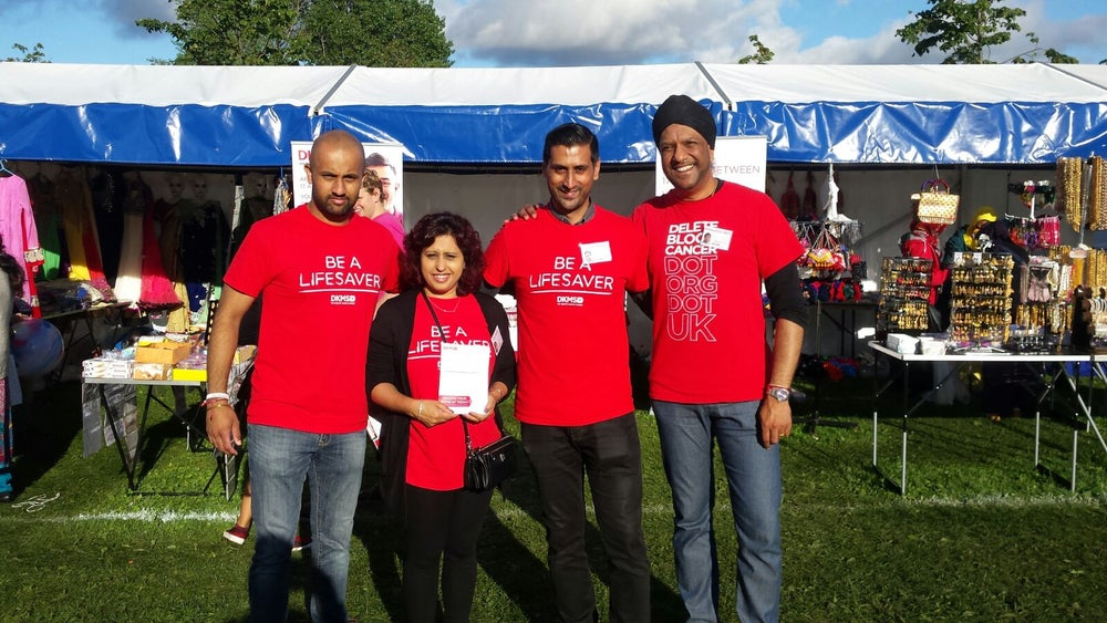 A group of four people stood outdoors wearing DKMS branded t-shirts