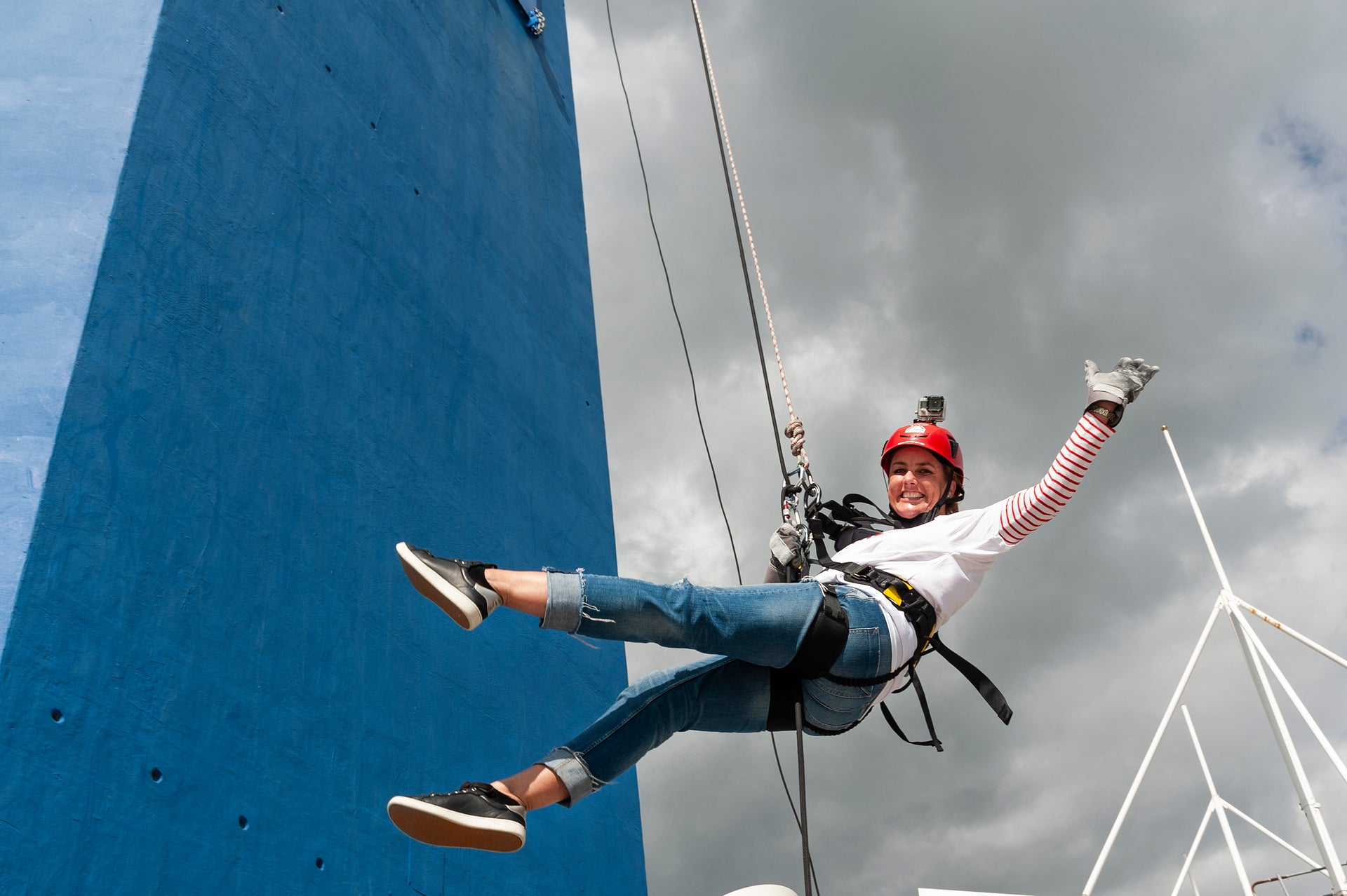 Sally on a harness waving to the camera as she abseils the Spinnaker Tower.