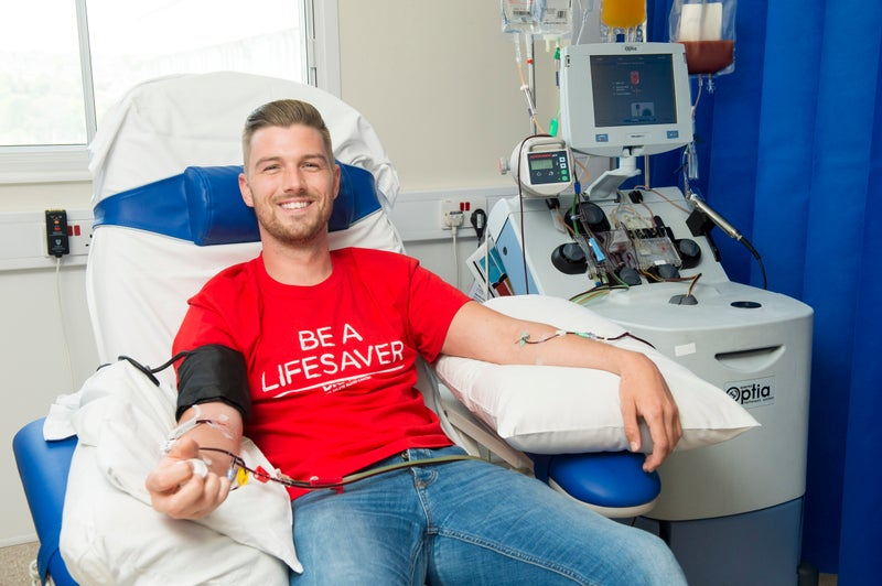 Person in a hospital chair, wearing a DKMS t-shirt, donating blood stem cells.