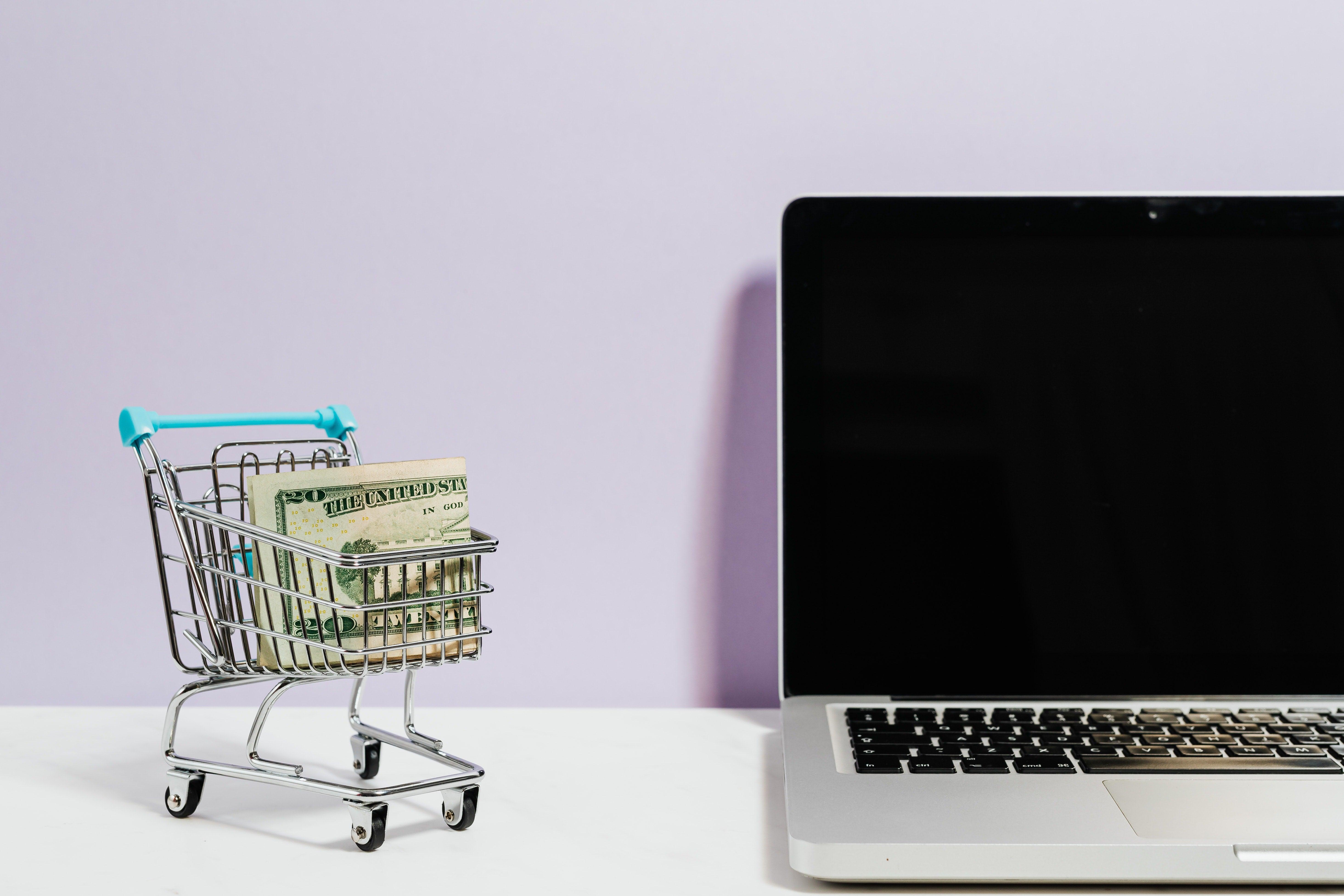 wat kan je B2B webshop leren van e-commerce giganten. Winkelkarretje met geld in, MacBook Pro.