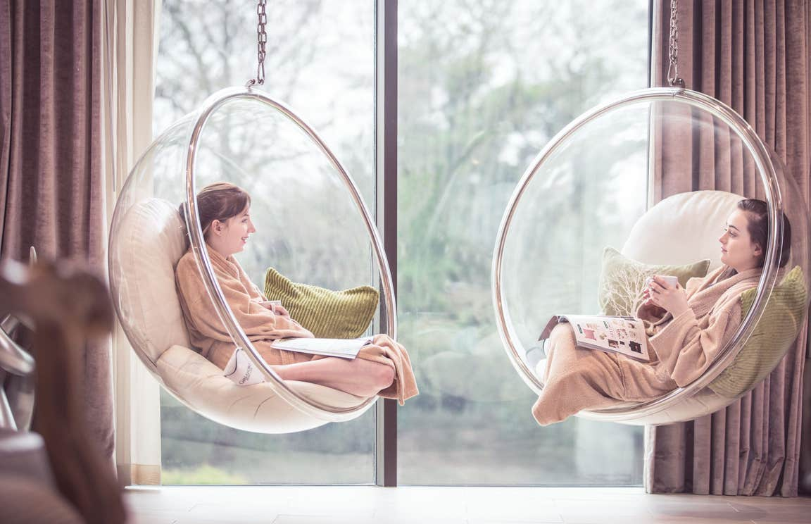 Two friends sitting in hanging chairs at a spa.