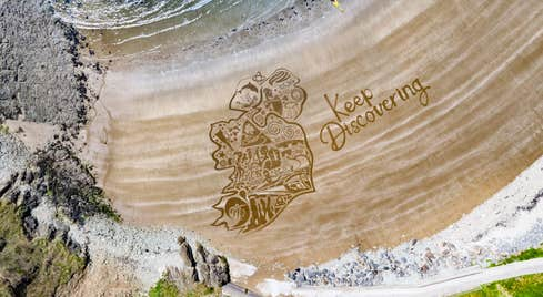 The Keep Discovering logo overlaid on golden sand at Kilmurrin Beach, County Waterford