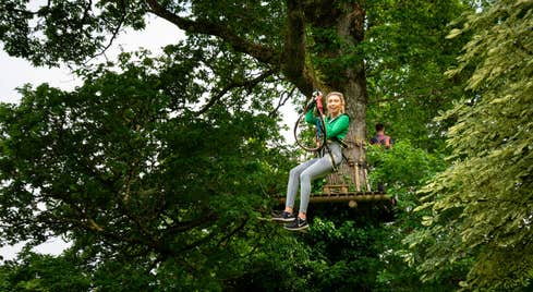 Girl in a green jumping sliding down a zipline in Roscommon